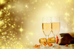 Glasses with champagne and bottle over sparkling holiday backgro Royalty Free Stock Photo