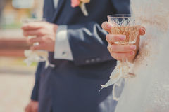 Glasses of champagne in brides and grooms hands. Royalty Free Stock Photo