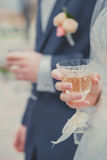 Glasses of champagne in brides and grooms hands. Royalty Free Stock Image