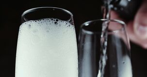 Glasses with champagne bubbles on dark background. Two wine glasses with champagne bubbles on dark background stock video footage