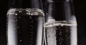 Glasses with champagne bubbles on dark background. Two wine glasses with champagne bubbles on dark background stock video