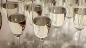 Glasses of champagne with bubbles. Champagne glasses with bubbles standing on the table stock footage