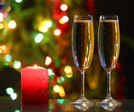 Glasses with champagne and candle against festive lights Stock Images