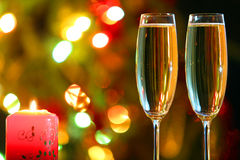 Glasses with champagne and candle against festive lights Royalty Free Stock Photography