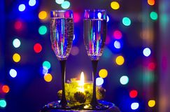 Champagne and a candle. Glasses of champagne and a candle with colorful background Royalty Free Stock Photography
