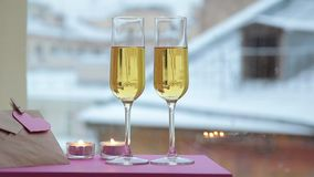 Glasses of champagne in candlelit on St Valentine's day. View of the snowy roofs stock video footage