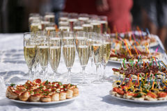 Glasses with champagne. catering banquet table. a lot of snacks and canapes Stock Image