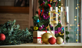 Glasses of champagne and christmas balls with lights in the background Stock Images