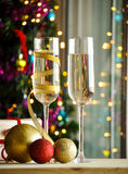 Glasses of champagne and christmas balls with lights in the background Royalty Free Stock Photo