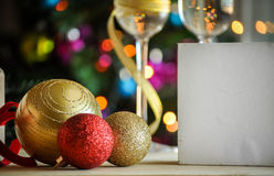 Glasses of champagne and christmas balls with lights in the background Royalty Free Stock Image