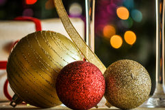 Glasses of champagne and christmas balls with lights in the background Royalty Free Stock Images