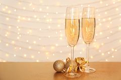 Glasses of champagne and Christmas balls. On table against blurred lights stock photography