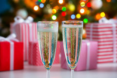 Glasses of champagne and Christmas gifts Stock Images