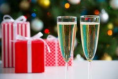 Glasses of champagne and Christmas gifts Royalty Free Stock Photos