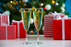 Glasses of champagne and Christmas gifts Stock Photos