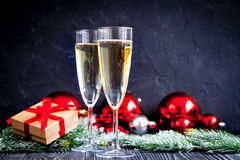 Glasses of champagne and Christmas ornaments on dark wooden background Royalty Free Stock Photography