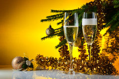 Glasses with champagne and Christmas ornaments Royalty Free Stock Photo