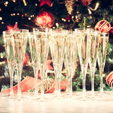 Glasses of champagne with Christmas tree background. Many glasse Royalty Free Stock Photos