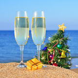 Glasses of champagne and Christmas tree on a beach. Glasses of champagne and decorated Christmas tree on the beach against the sky and blue sea Royalty Free Stock Images