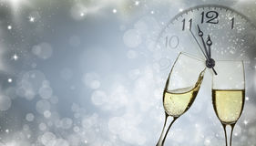 Glasses with champagne and clock close to midnight. Glasses with champagne against holiday lights and clock close to midnight Royalty Free Stock Photo