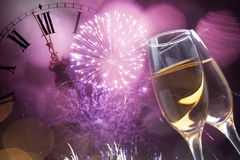 Glasses with champagne and clock close to midnight. Glasses with champagne against holiday lights and clock close to midnight Stock Image