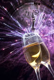 Glasses with champagne and clock close to midnight. Glasses with champagne against holiday lights and clock close to midnight Royalty Free Stock Images