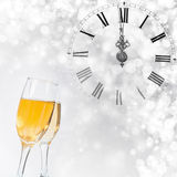 Glasses with champagne and clock close to midnight. Glasses with champagne against holiday lights and clock close to midnight Stock Photography