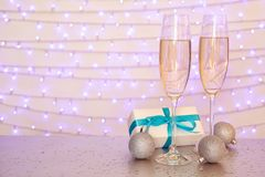 Glasses of champagne, decorative balls and Christmas gift. On table against blurred lights Stock Photos