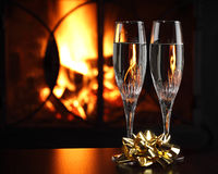 Glasses with champagne, fire as the background Stock Photos