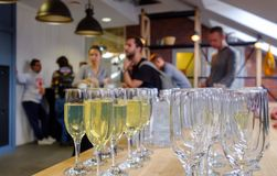 Glasses with champagne in the foreground, blurred people on the background. Stock Photo