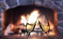 Glasses of champagne in front of warm fireplace Stock Image