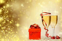 Glasses with champagne and gift box over sparkling holiday backg Stock Image