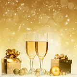 Glasses with champagne and gift box over sparkling holiday backg Royalty Free Stock Image