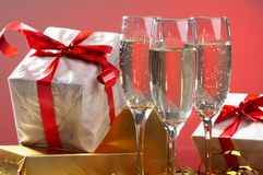 Glasses of champagne, gifts with red tapes Royalty Free Stock Image