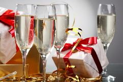 Glasses of champagne, gifts with red tapes Stock Image