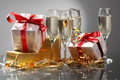 Glasses of champagne, gifts with red tapes Royalty Free Stock Photography