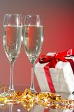 Glasses of champagne, gifts with red tapes Stock Photos