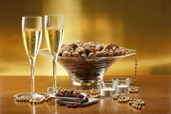 Glasses of champagne with gold background. With walnuts, candels and dried raisins Stock Image