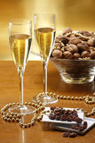 Glasses of champagne with gold background walnuts. And dryed raisins Royalty Free Stock Images