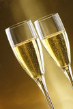 Glasses of champagne with gold background walnuts. And dryed raisins Stock Photo