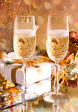 Glasses of champagne with gold ribbon gifts Royalty Free Stock Images
