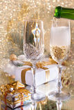 Glasses of champagne with gold ribbon gifts Stock Photos