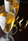 Glasses of champagne and gold streamer. Two glasses of champagne and gold streamer over black background Stock Image