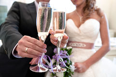 Glasses with champagne in the hands of the bride and groom. Royalty Free Stock Photography