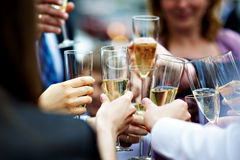 Glasses of champagne in hands of guests at wedding royalty free stock photography