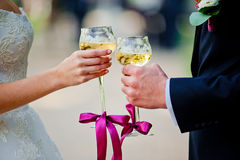 Glasses with champagne in hands newlyweds. Two glasses of champagne in the hands of the newlyweds stock images