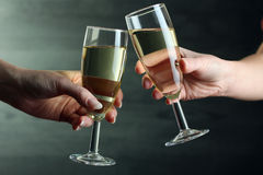 Glasses of champagne in hands Stock Photos