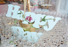 Glasses of champagne and Happy decoration on festive table Stock Photography
