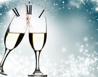 Glasses of champagne at New Year's Eve. Glasses with champagne against fireworks and clock close to midnight Stock Photo