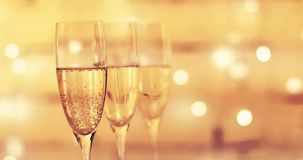 Glasses of champagne over flashing bokeh background stock footage